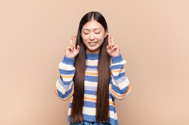 Jovem asiática se sentindo nervosa e esperançosa, cruzando os dedos isolada