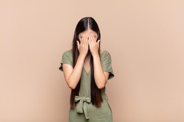 Jovem asiática se sentindo triste, frustrada, nervosa e deprimida, cobrindo o rosto com as duas mãos, chorando
