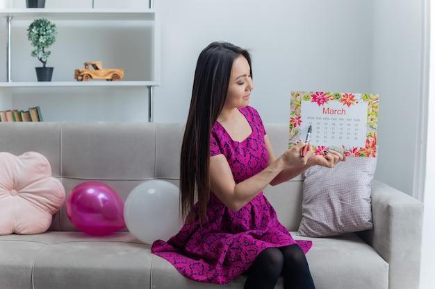 Jovem asiática segurando o calendário de papel do mês de março, apontando com uma caneta no encontro, sentada em um sofá, sorrindo alegremente na luz da sala de estar, comemorando o dia internacional das mulheres.