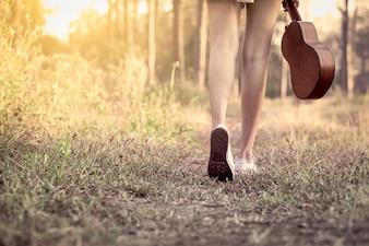 Jovem asiática, segurando ukelele e caminhando no parque em tom de cor vintage