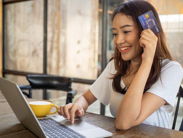 Jovem asiática segurando um cartão de crédito