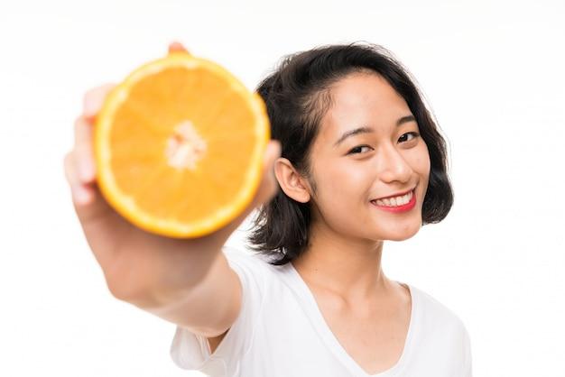 Jovem asiática segurando uma laranja