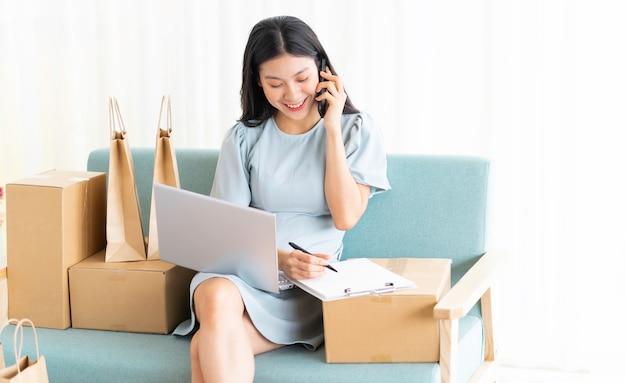 Jovem asiática sentada em casa vendendo online