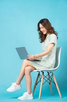 Jovem asiática sentada em uma cadeira usando um laptop com uma expressão feliz