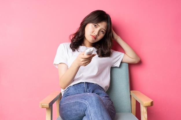Jovem asiática sentada no sofá assistindo televisão sozinha