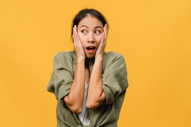 Jovem asiática sente felicidade com uma expressão positiva, alegre surpresa funky, vestida com um pano casual, isolado na parede amarela. mulher feliz adorável feliz alegra sucesso. expressão facial.