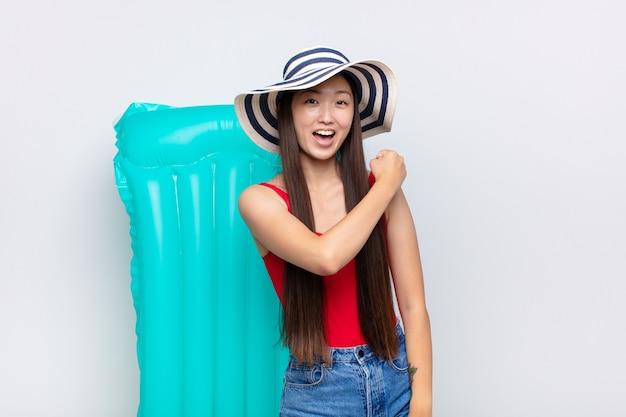 Jovem asiática sentindo-se feliz, positiva e bem-sucedida, motivada para enfrentar um desafio ou comemorar bons resultados