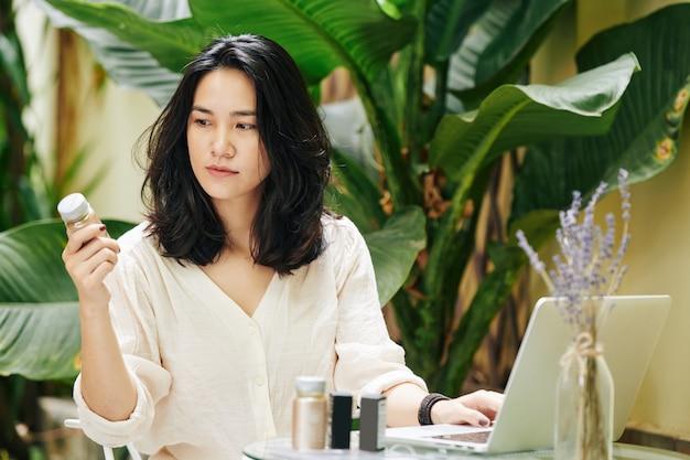 Jovem asiática séria olhando para os cosméticos que ela encomendou na loja online