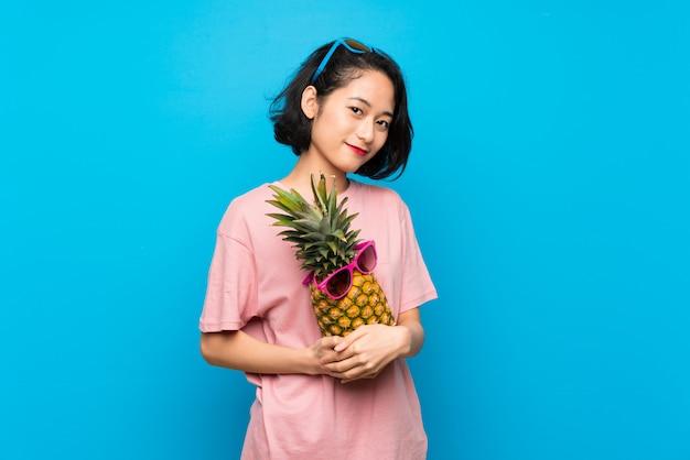 Jovem asiática sobre azul isolado segurando um abacaxi com óculos de sol
