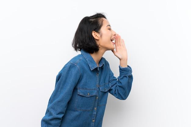 Jovem asiática sobre gritos brancos isolados com a boca aberta para a lateral