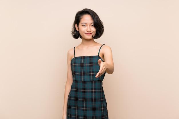 Jovem asiática sobre parede amarela isolada, apertando as mãos para fechar um bom negócio