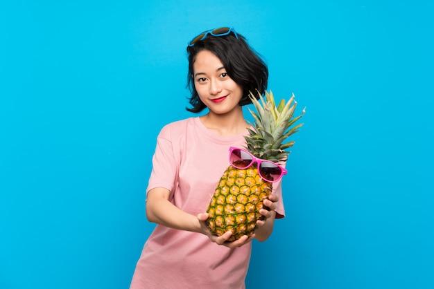 Jovem asiática sobre parede azul isolada, segurando um abacaxi com óculos de sol