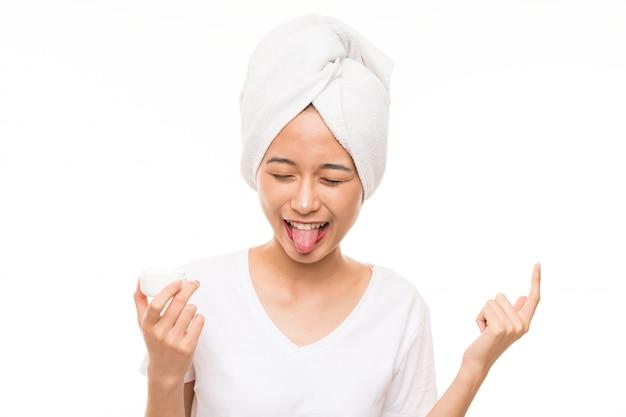Jovem asiática sobre parede isolada com creme hidratante