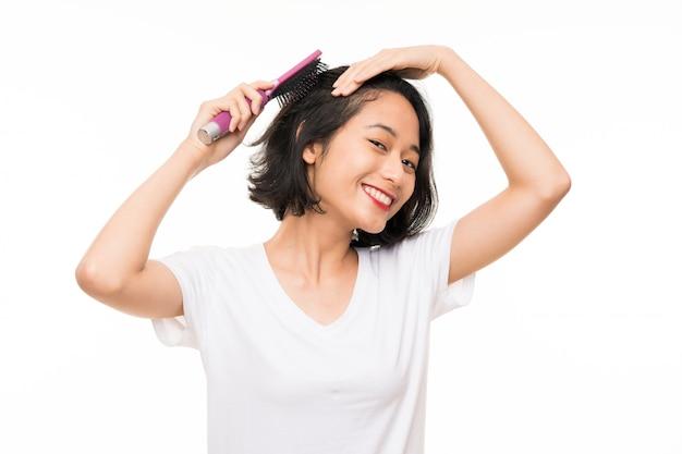 Jovem asiática sobre parede isolada com pente de cabelo