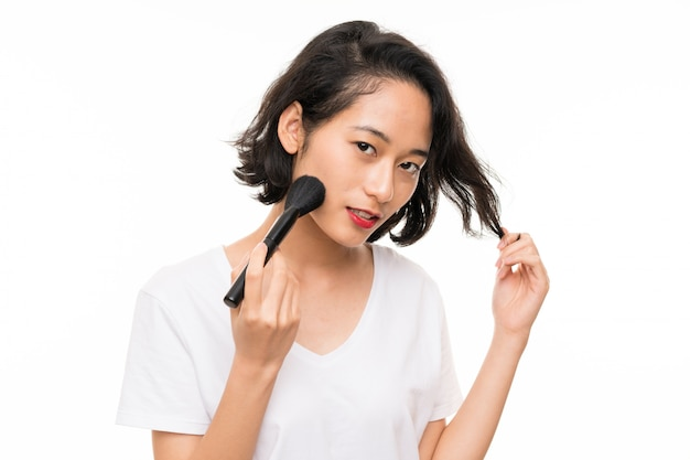 Jovem asiática sobre parede isolada com pincel de maquiagem
