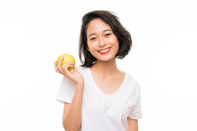 Jovem asiática sobre parede isolada com uma maçã