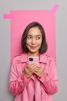 Jovem asiática sonhadora e sonhadora conversando com amigos no celular, usando um gadget legal e um aplicativo vestido com uma jaqueta posa contra uma parede cinza com papel gesso rosa