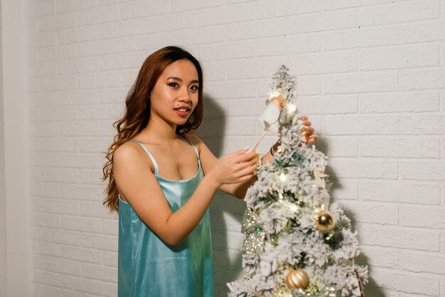 Jovem asiática sorridente com uma caixa de presente de natal perto da árvore de natal