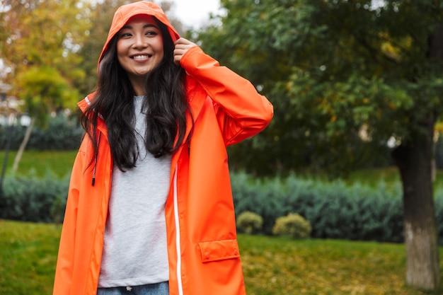 Jovem asiática sorridente usando capa de chuva e caminhando ao ar livre na chuva