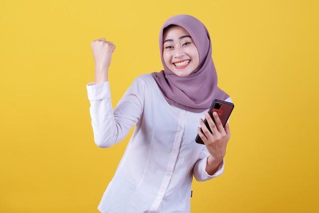 Jovem asiática sorridente usando hijab, mostrando o celular fazendo gesto de sim