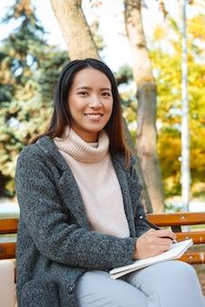 Jovem asiática sorridente, vestindo um casaco, sentada em um banco do parque, fazendo anotações em um bloco de notas