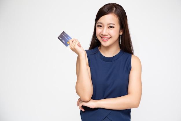 Jovem asiática sorrindo e segurando o cartão de crédito