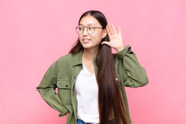 Jovem asiática sorrindo, olhando curiosamente para o lado, tentando ouvir uma fofoca ou ouvindo um segredo