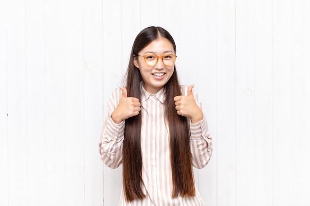 Jovem asiática sorrindo, parecendo feliz, positiva e isolada