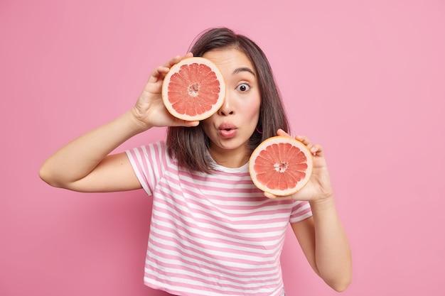 Jovem asiática surpreendida posa com frutas cítricas dentro de casa segurando duas metades de toranja fresca para manter uma nutrição saudável e expressão chocada vestida com uma camiseta isolada sobre a parede rosa