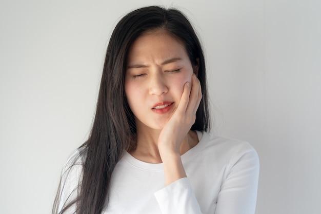 Jovem asiática tocando a bochecha e sentindo dor de dente