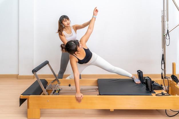 Jovem asiática trabalhando em uma máquina reformadora de pilates com sua treinadora durante o treinamento de exercícios de saúde