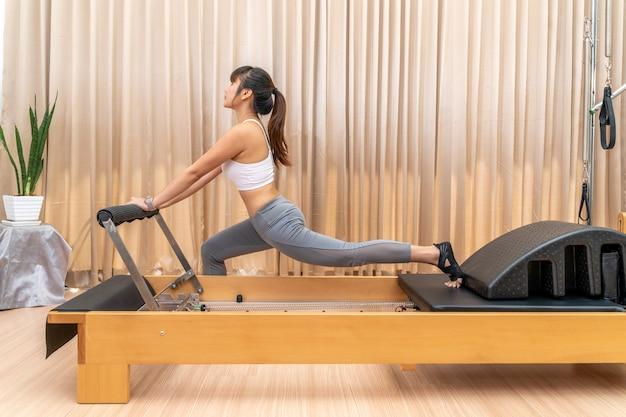 Jovem asiática trabalhando em uma máquina reformadora de pilates durante seu treinamento de exercícios de saúde para esticar as pernas