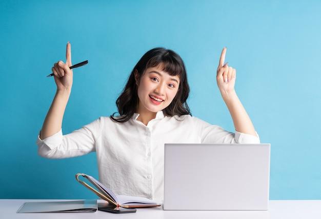 Jovem asiática trabalhando no azul