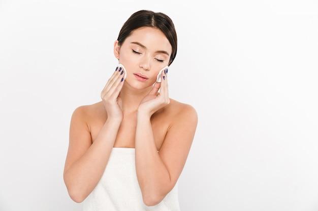 Jovem asiática usando esponjas para remover maquiagem isolado