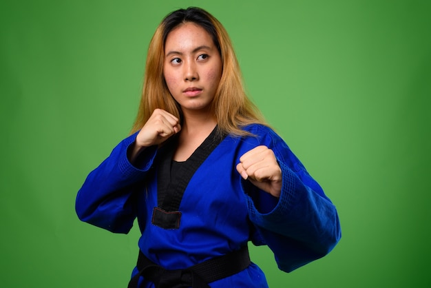 Jovem asiática usando karatê azul contra o espaço verde