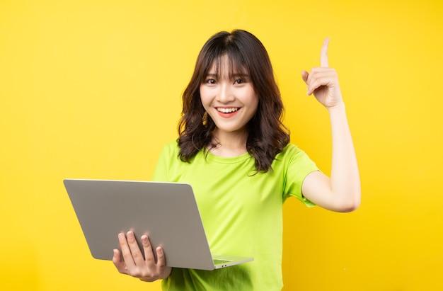 Jovem asiática usando laptop na parede amarela