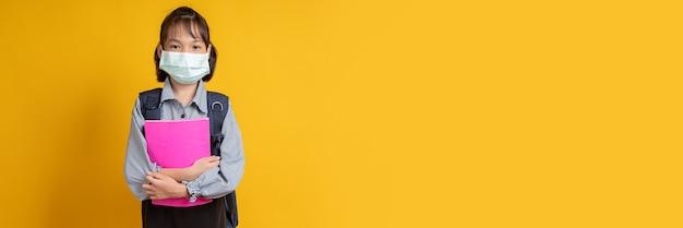 Jovem asiática usando máscara facial em estúdio em amarelo