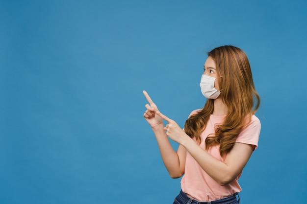 Jovem asiática usando máscara médica mostra algo no espaço em branco com um vestido casual e olhando para frente, isolado na parede azul
