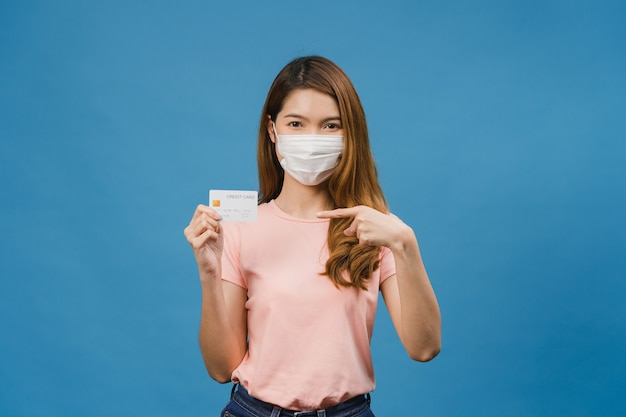 Jovem asiática usando máscara médica mostra cartão do banco de crédito com expressão positiva, sorri amplamente, vestida com roupas casuais, sentindo felicidade e parada isolada na parede azul