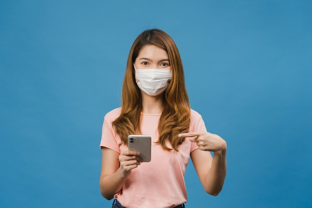 Jovem asiática usando máscara médica usando um telefone celular com roupas casuais isoladas na parede azul