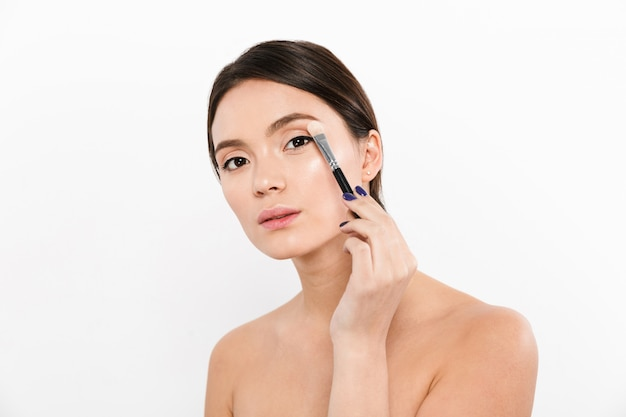 Jovem asiática usando o pincel para aplicar maquiagem isolado