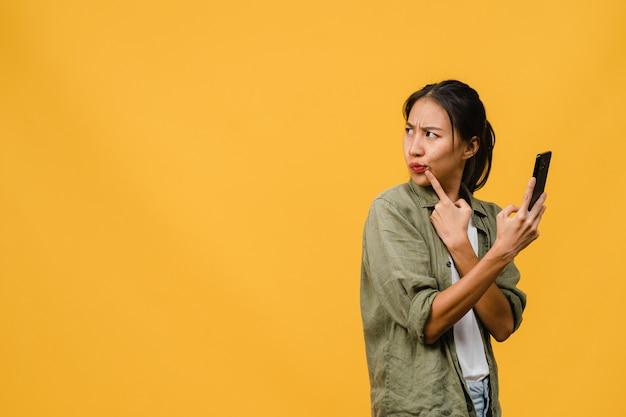 Jovem asiática usando telefone com expressão positiva, vestida com um pano casual na parede amarela