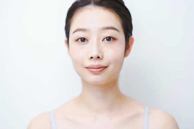 Jovem asiática verificando as condições de sua pele