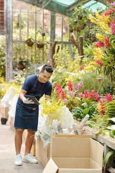 Jovem asiático alegre, gostando de trabalhar no jardim do viveiro, ele está desempacotando caixas de flores e verificando a documentação no computador tablet