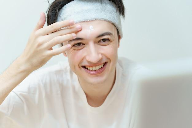 Jovem asiático aplicando creme no rosto