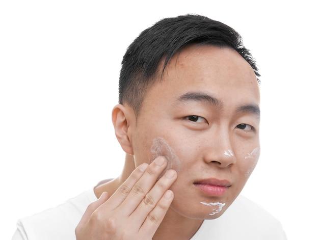 Jovem asiático aplicando creme para pele com problema no rosto, em fundo branco