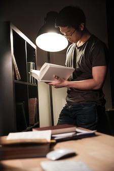 Jovem asiático atraente de óculos em pé e lendo um livro à noite