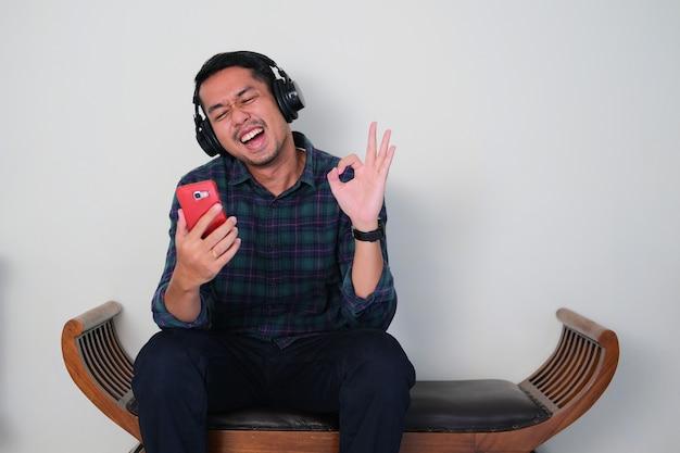 Jovem asiático atraente sentado em um sofá enquanto ouve música usando um fone de ouvido