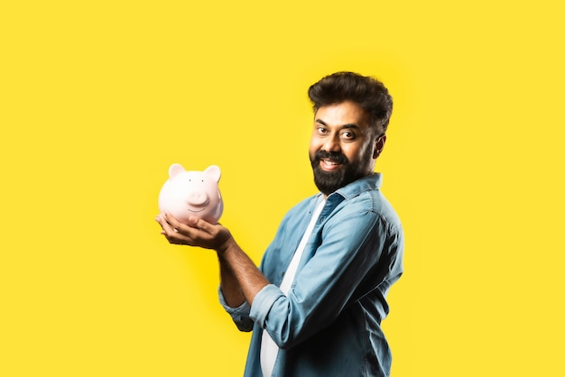 Jovem asiático barbudo indiano segurando o cofrinho em amarelo. conceito de pessoas e finanças