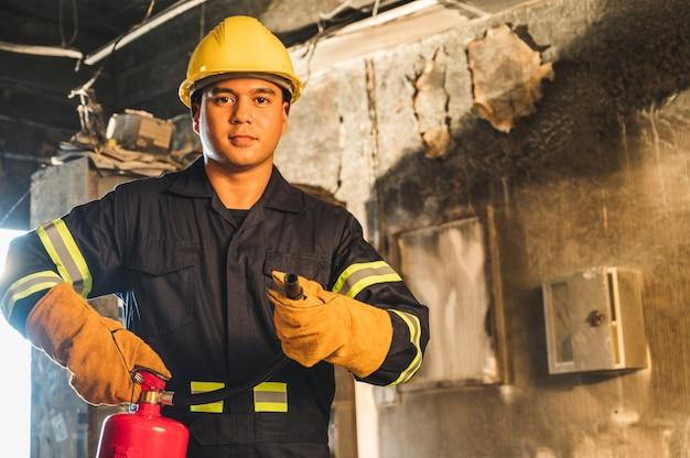 Jovem asiático bombeiro, bombeiros usam extintores que estão queimando no edifício.